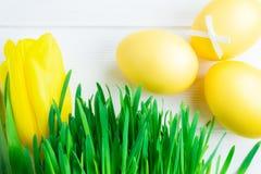 Oeufs de pâques colorés, verts décoratifs et tulipe sur le fond en bois blanc photo libre de droits
