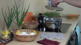 Oeufs de pâques de colorant de main de femme avec les chutes matérielles dans la cuisine 4K banque de vidéos