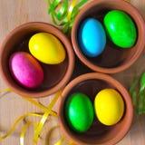 Oeufs de pâques décorés colorés dans des cuvettes d'argile Photo libre de droits