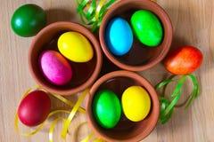 Oeufs de pâques décorés colorés dans des cuvettes d'argile Image libre de droits