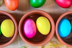 Oeufs de pâques décorés colorés dans des cuvettes d'argile Photos stock