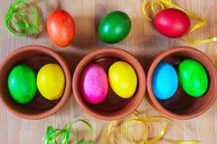Oeufs de pâques décorés colorés dans des cuvettes d'argile Images stock