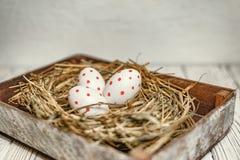 Oeufs de pâques décorés dans un nid dans une boîte en bois sur un fond clair photos libres de droits