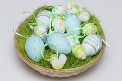 Oeufs de pâques décorés dans un panier peu profond Photo libre de droits