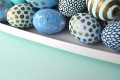 Oeufs de pâques décorés dans une cuvette, plan rapproché sur le fond en pastel Photo stock