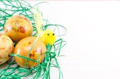 Oeufs de pâques décorés en paille verte Photos stock