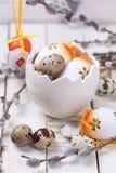 Oeufs de pâques décoratifs dans des branches de cuvette et de saule sur en bois Images libres de droits
