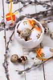 Oeufs de pâques décoratifs dans des branches de cuvette et de saule sur en bois Image libre de droits