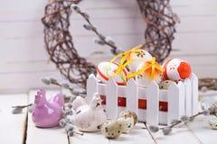 Oeufs de pâques décoratifs dans la boîte, les poules et les branches de saule sur W Photo libre de droits