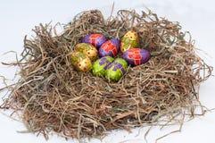 Oeufs de pâques décoratifs de chocolat dans le nid Photo stock