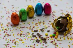 Oeufs de pâques d'or cassés de chocolat avec des chocolats colorés à l'intérieur sur le fond blanc avec les confettis brouillés c images stock