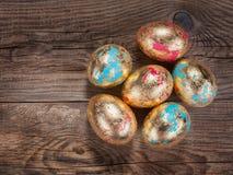Oeufs de pâques d'or sur le vieux conseil images stock