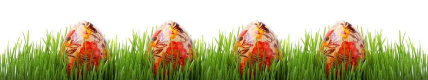 Oeufs de pâques dans l'herbe d'isolement sur le blanc Photo stock