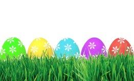 Oeufs de pâques dans l'herbe verte d'isolement sur le blanc Image libre de droits