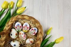 Oeufs de pâques dans la décoration fabriquée à la main de decoupage avec les tulipes jaunes Photos libres de droits