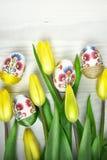Oeufs de pâques dans la décoration fabriquée à la main de decoupage avec les tulipes jaunes Image stock