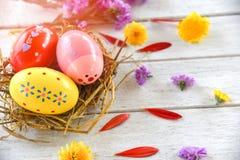 Oeufs de pâques dans la décoration de nid avec le fond blanc de ressort de pétale coloré de fleurs photos libres de droits