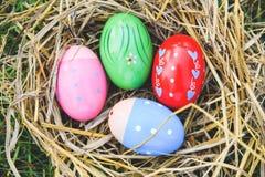 Oeufs de pâques dans la tradition de fête décorée colorée de magot sur l'herbe verte images libres de droits