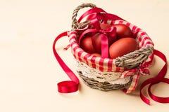 Oeufs de pâques dans le nid blanchâtre et les fleurs blanches Photographie stock