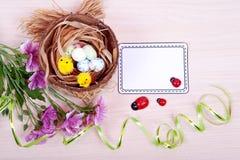 Oeufs de pâques dans le nid sur les planches en bois rustiques Photo stock