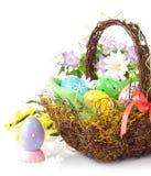 Oeufs de pâques dans le panier avec des fleurs de source Photos stock