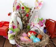 Oeufs de pâques dans le panier et deux Bunny Tilda Image stock