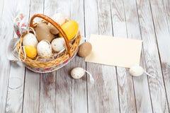 Oeufs de pâques dans le panier sur les planches en bois rustiques Carte de Pâques avec la feuille blanche vide Photo stock