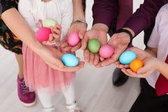 Oeufs de pâques dans les mains de la famille Image stock