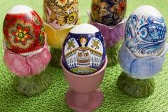Oeufs de pâques dans les supports colorés Images stock