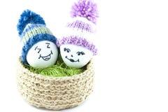 Oeufs de pâques dans un panier Émoticônes dans des chapeaux tricotés avec des pom-poms Images libres de droits
