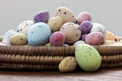 Oeufs de pâques dans un panier en osier Photographie stock libre de droits