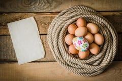 Oeufs de pâques dans un panier fait à partir de la corde Image stock