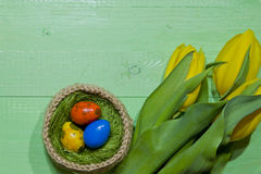 Oeufs de pâques dans un panier Oeufs de caille peints Un bouquet de jaune Photographie stock libre de droits