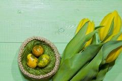 Oeufs de pâques dans un panier Oeufs de caille peints Un bouquet de jaune Photo stock