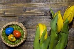 Oeufs de pâques dans un panier Oeufs de caille peints Un bouquet de jaune Photo libre de droits