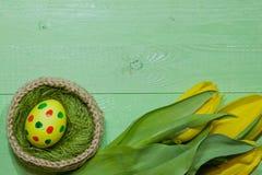 Oeufs de pâques dans un panier Oeufs peints Un bouquet de tulipe jaune Photos stock