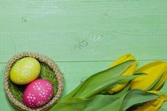 Oeufs de pâques dans un panier Oeufs peints Un bouquet de tulipe jaune Photographie stock libre de droits