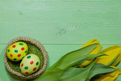 Oeufs de pâques dans un panier Oeufs peints Un bouquet de tulipe jaune Images stock