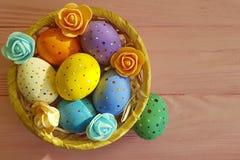 Oeufs de pâques dans un panier, paille, espace chromatique en bois Photographie stock libre de droits
