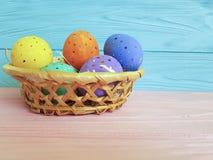 Oeufs de pâques dans un panier, paille, l'espace coloré en bois de printemps Image stock
