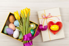 Oeufs de pâques dans une boîte avec les tulipes colorées Photo stock