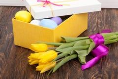 Oeufs de pâques dans une boîte avec les tulipes colorées Image stock