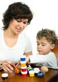 Oeufs de pâques de peinture de bébé de whith de maman Photos libres de droits