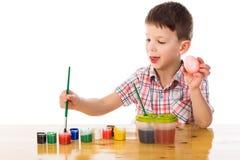 Oeufs de pâques de peinture de petit garçon Photographie stock libre de droits