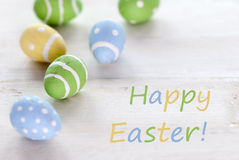 Oeufs de pâques de vert bleu et de jaune avec le texte anglais Joyeuses Pâques Photos libres de droits