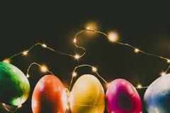 Oeufs de pâques de différentes couleurs sur un fond noir et des lumières images stock