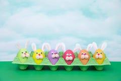Oeufs de pâques drôles de lapin de visages dans un carton d'oeufs sur le ciel bleu de table verte Photo libre de droits
