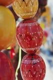 Oeufs de pâques en bois rouges et jaunes au-dessus de fond brouillé Image libre de droits