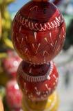 Oeufs de pâques en bois rouges et jaunes au-dessus de fond brouillé Photographie stock libre de droits