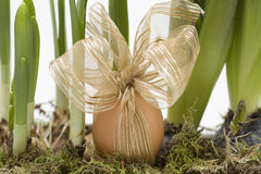 Oeufs de pâques en paille avec des fleurs Photographie stock